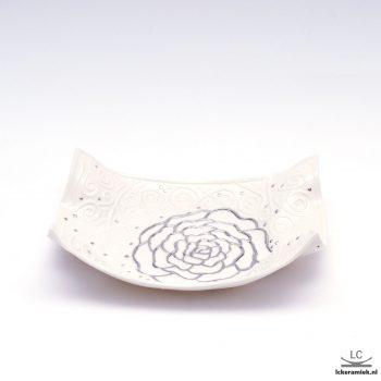 Porseleinen schaal met een zilveren roos